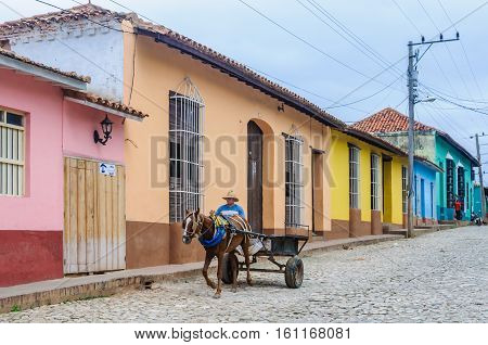 TRINIDAD, CUBA - MARCH 23, 2016: Man riding a horse carriage on the cobblestone streets in the UNESCO World Heritage old town of Trinidad Cuba