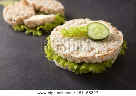 Round rice crispbreads with cucumber and lettuce on table, closeup