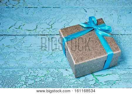 Gift birthday Christmas present concept - silver gift box with blue ribbon on blue painted wooden background