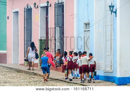 TRINIDAD, CUBA - MARCH 23, 2016: Pioneer kids walking on the cobblestone streets in the UNESCO World Heritage old town of Trinidad Cuba