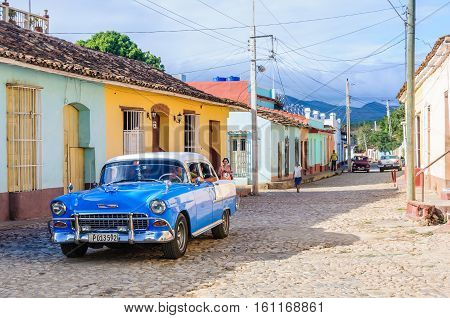 TRINIDAD, CUBA - MARCH 23, 2016: Old automobile parked in front of colorful houses on the cobblestone streets of the UNESCO World Heritage old town in Trinidad Cuba