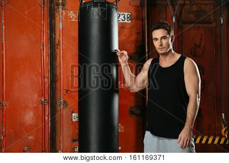 Portrait of strong boxer standing in a gym near punch bag. Looking at camera.
