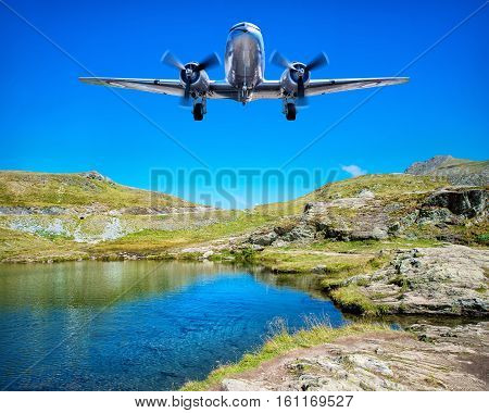 airplane flying over a lake in the mountains