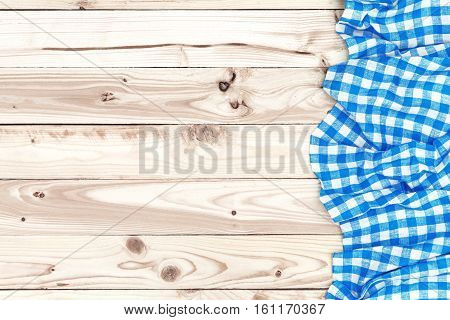 Blue checkered tablecloth on a light wooden table, top view