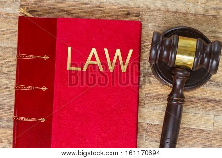 Wooden Law Gavel and legal book on wooden desktop with word Law, top view