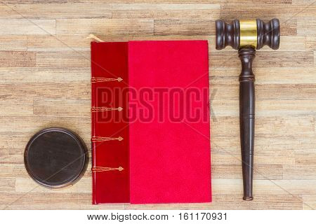 Wooden Law Gavel and red legal book on wooden table desktop, top view