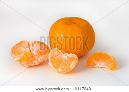 Peeled tangerine is photographed on a white background