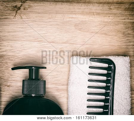 Hair care and styling background. Hair beauty product, wide tooth comb, towel on wooden surface. Copy space. Toned image