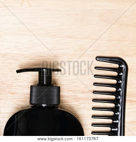 Hair care and styling background. Hair beauty product and wide tooth comb on wood surface. Copy space