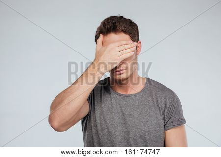 Portrait of a young casual man covering eyes with hand isolated on the gray background