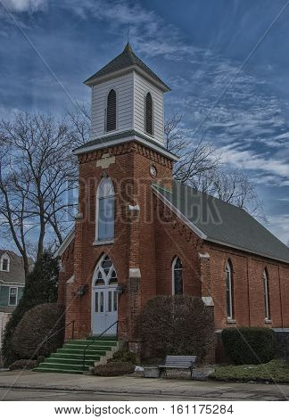 Photograph of a beautiful old brick church beneath a pleasant winter sky in a rural Wisconsin town.