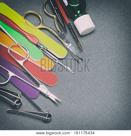 Manicure tools on gray textured surface. Copy space. Retro style processing