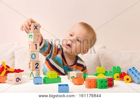 Portrait of child playing with wooden cubes with numbers and colorful plastic bricks at the table. Toddler having fun and building out of constructor bricks. Early learning. Developing toys