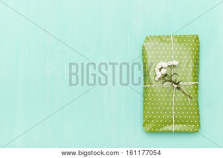 Top view on nice wrapped gift with flowers on turquoise wooden background. Present for birthday Christmas and any other celebration. Holidays concept