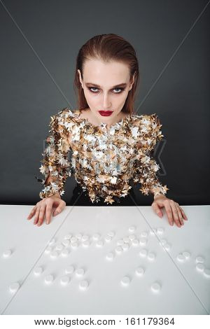 Beautiful young woman sitting at the table with big pills