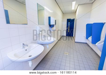 Toilet room for boys with urinals sinks and mirrors on high school