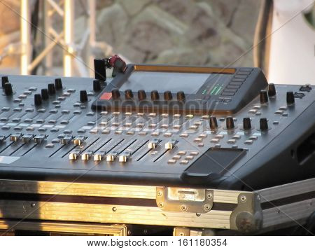 Professional audio mixing console with faders and adjusting knobs for party outdoor at sunset