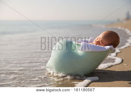 newborn baby boy on the sandy ocean beach. Newborn baby in the nutshell on the sea shore on sunny day. Motherhood and childhood concept.