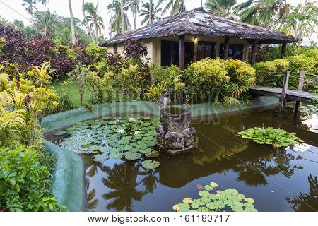 Tropical paradise - bungalows near the ornamental pond with white water lilies surrounded by tropical plants and wooden bridges. Fiji Islands.