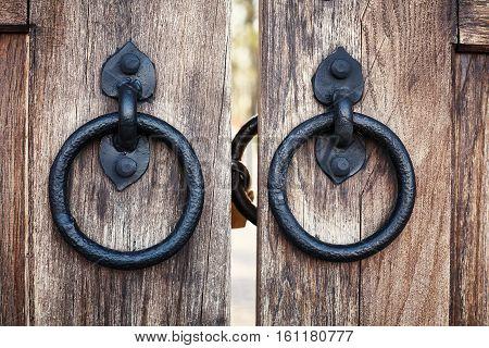 Old style metal door handle knocker on wooden background