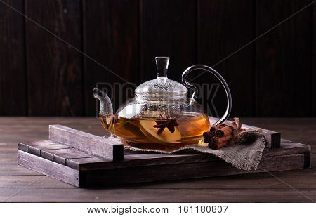 Hot fruit tea with ripe pears and cinnamon, delicious and aromatic. Transparent tea pot and cup on old wooden rustic background