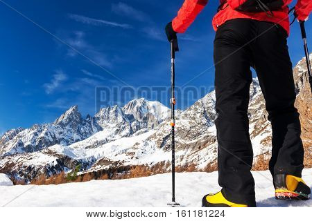 Hiker takes a rest looking at Mont Blanc panorama during the famous winter trekking Tour du Mont Blanc. Mont Blanc massif, Courmayer, Italy.