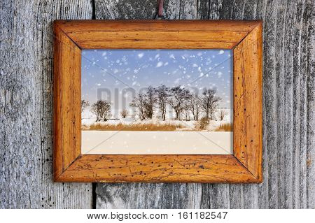 Frame with winter landscape on a wooden background