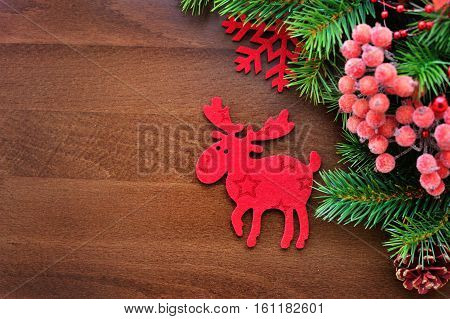 Christmas Figurine Elk And Spruce Twigs On A Wooden Background