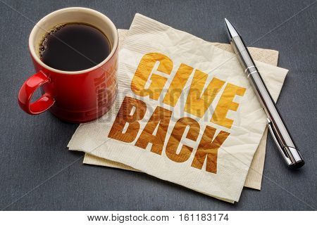 Give back word abstract on napkin  with cup of coffee against gray slate stone background