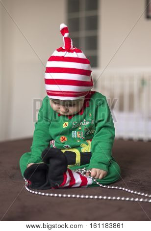 child in a Santa's helper elf costume with beads