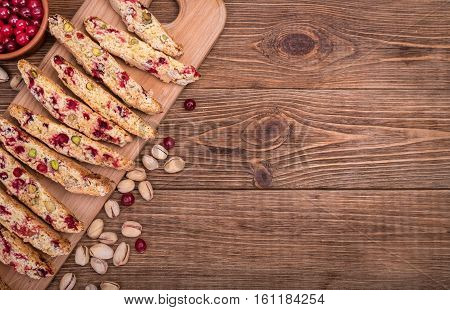 Biscotti with pistachios and cranberries on the wooden table .