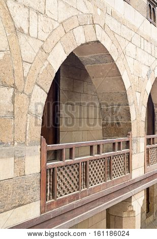 Angled view of one arch with interleaved wooden balustrades at the arcade surrounding the courtyard of caravansery (Wikala) of al-Ghuri Medieval Cairo Egypt