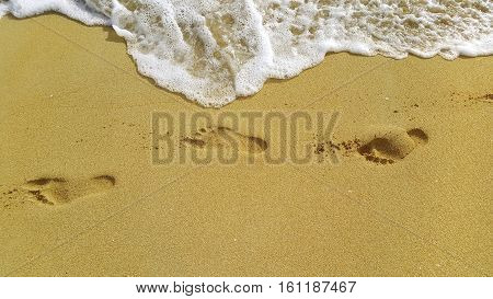 Nature background with sea foam and footprints in the sand