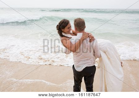The Bride And Groom Have Fun On Wedding On The Ocean Sand Beach