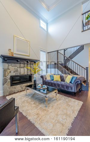 Beautiful and large living room interior with hardwood floors and vaulted ceiling in new luxury home. View of entryway, and second story loft style area