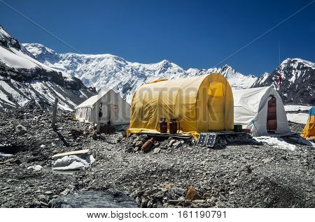 Tents of hikers on rocky ground surrounded by mountain range near South Inylcheck Glaciar in Kyrgystan.