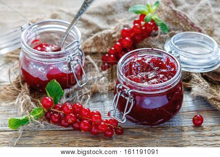 Old Table With Red Currants And A Jar Of Homemade Jam.