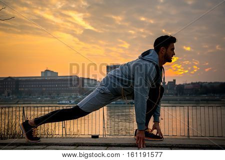 A handsome young man stretching and warming up on the riverside with the sun setting behind him
