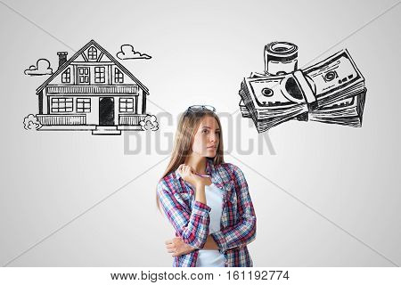 Attractive caucasian girl on grey background with house and money sketch. Real estate mortgage and housing concept