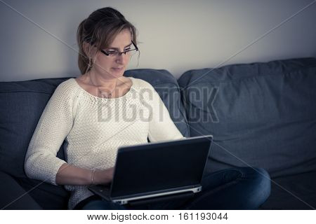 Middle-aged woman using laptop at home