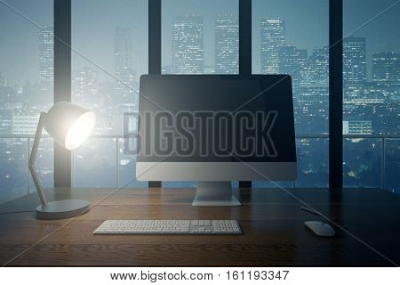 Workspace at night. Front view of wooden desktop with blank computer monitor keyboard and table lamp on city background. Mock up 3D Rendering