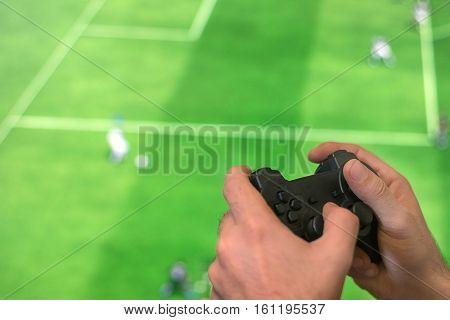 Hand Holding Game Controller Playing Football Game.