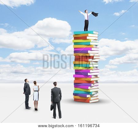 Group of businesspeople looking up to successful businessman standing on pile of book. Sky background. Education and success concept