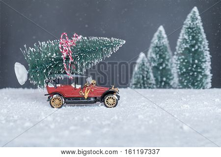 small retro car with Christmas tree on the roof going on holiday