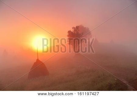 Sunrise Over Mountain Field. Haystacks In Misty Autumn Morning Hills.