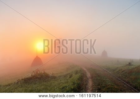 Sunrise Over Mountain Field. Haystacks And Road  In Misty Autumn Morning Hills.