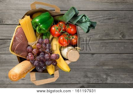 Paper bag of groceries on wooden table with copy space top view