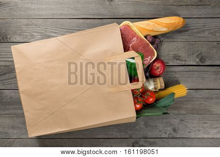 Paper bag full of different food on wooden background close up. Grocery shopping concept top view