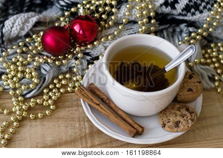 Fresh green tea with cinnamon sticks and homemade chocolate cookies red christmas balls and golden beads knitted blanket on wooden table