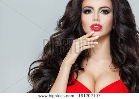 Attractive Model with Dark Curly Hair Red Lips Makeup and Red Bra. Brunette Woman with Perfect Hairstyle and Makeup